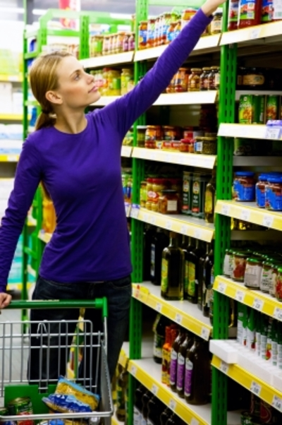 Woman Comparing Prices in Supermarket